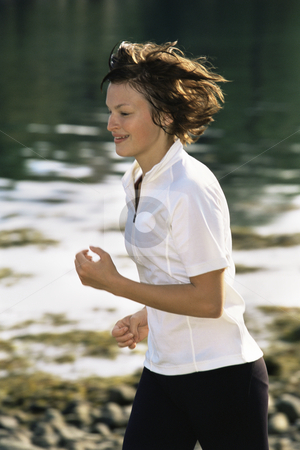 Young woman running along water's edge stock photo,  by Monkey Business Images