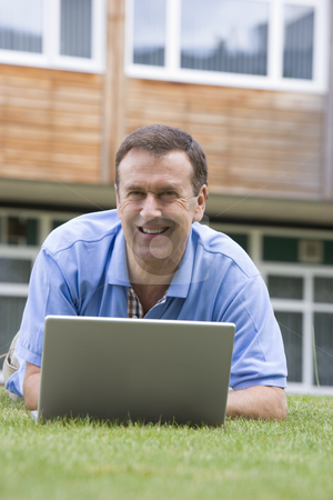 Man using laptop while lying in grass on campus stock photo,  by Monkey Business Images