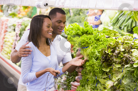 Couple shopping in produce department stock photo, Couple shopping in supermarket produce department by Monkey Business Images
