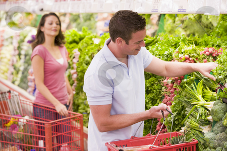 Couple flirting in supermarket aisle stock photo, Young couple flirting in supermarket aisle by Monkey Business Images