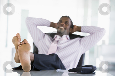Businessman sitting in office with feet on desk relaxing and smi stock photo,  by Monkey Business Images