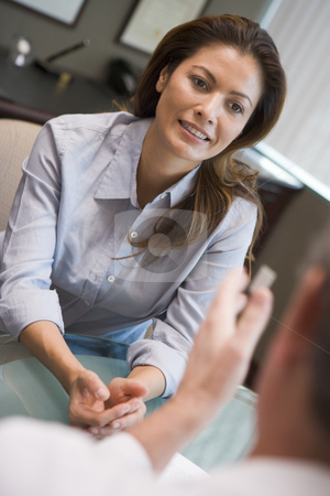 Woman having meeting with doctor in IVF clinic stock photo, Woman having meeting with doctor in IVF clinic sitting at desk by Monkey Business Images
