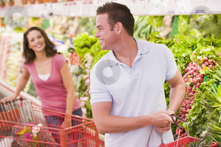 Couple flirting in supermarket stock photo, Couple flirting in supermarket aisle by Monkey Business Images