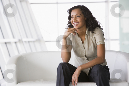 Businesswoman sitting on sofa in lobby stock photo, Businesswoman sitting on sofa in lobby in office by Monkey Business Images
