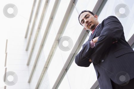 Businessman standing outside office block stock photo, Businessman standing outside office block looking to camera by Monkey Business Images