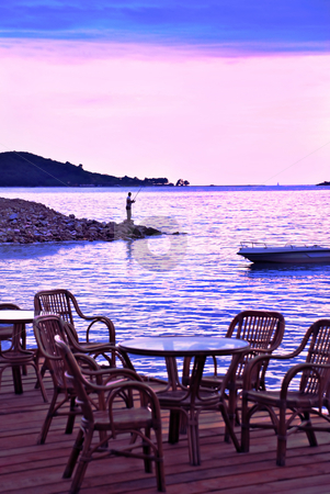 Evening seaside in pink and blue stock photo, Pink sunset from wooden terrace, man fishing by Julija Sapic