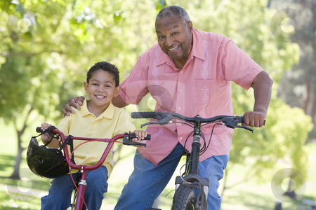Grandfather and grandson on bikes outdoors smiling stock photo,  by Monkey Business Images