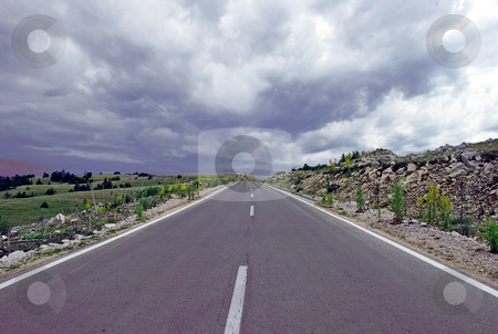 Way into cloudy sky stock photo, Gray road through mountain landscape under cloudy sky by Julija Sapic