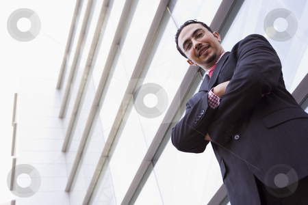 Businessman standing outside office building stock photo, Businessman standing outside office building looking to camera by Monkey Business Images