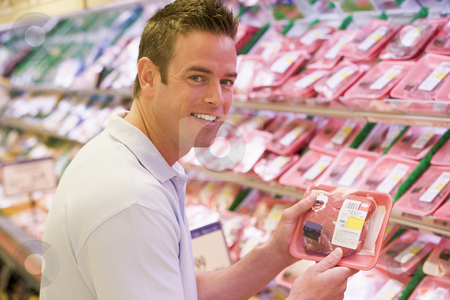 Man buying fresh meat stock photo, Man buying fresh meat from supermarket counter by Monkey Business Images