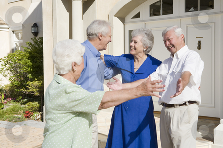 Senior couple greeting friends stock photo, Senior couple greeting friends outside house by Monkey Business Images