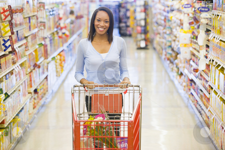 Woman pushing trolley in supermarket stock photo, Woman pushing trolley along aisle in supermarket by Monkey Business Images