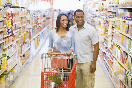 Couple shopping in supermarket stock photo, Couple shopping in supermarket grocery aisle by Monkey Business Images