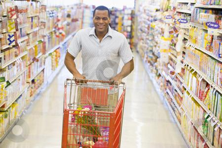 Man pushing trolley along supermarket aisle stock photo, Man pushing trolley along supermarket grocery aisle by Monkey Business Images