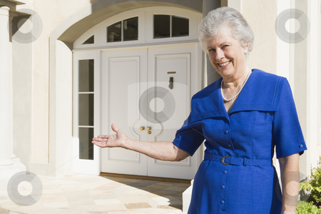 Senior woman standing outside home stock photo, Senior woman welcoming guests to home by Monkey Business Images