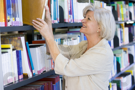 Senior woman pulling a library book off shelf stock photo,  by Monkey Business Images