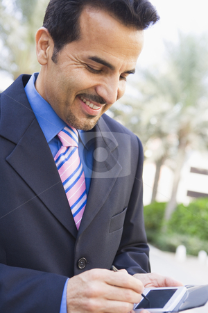 Businessman using PDA stock photo, Businessman using PDA outside by Monkey Business Images
