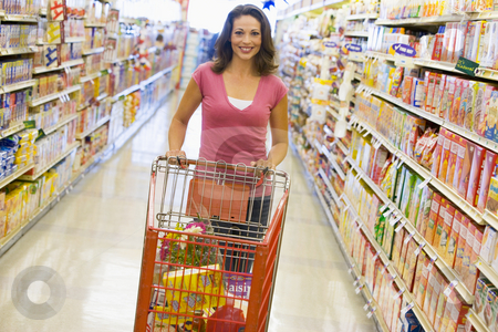 Woman pushing trolley along supermarket aisle stock photo, Woman pushing trolley along supermarket grocery aisle by Monkey Business Images