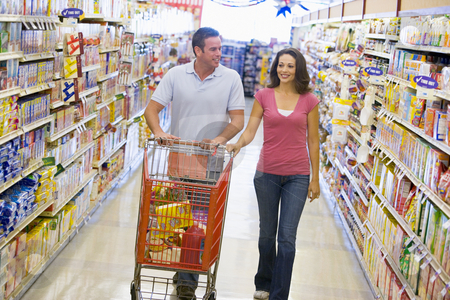Couple shopping in supermarket aisle stock photo, Couple shopping in supermarket grocery aisle by Monkey Business Images