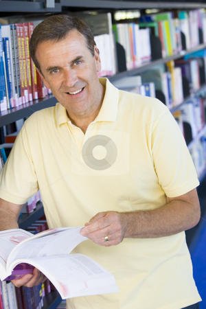 Man reading in a library stock photo,  by Monkey Business Images