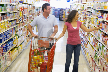 Couple shopping in supermarket stock photo, Couple in shopping in supermarket grocery aisle by Monkey Business Images