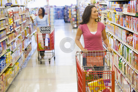 Two women shopping in supermarket stock photo, Two women pushing trolleys along supermarket aisle by Monkey Business Images