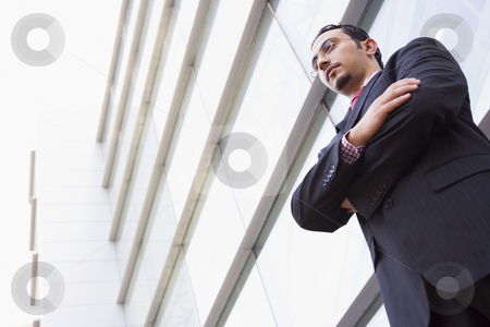 Businessman standing outside modern office stock photo, Businessman standing outside modern office building by Monkey Business Images