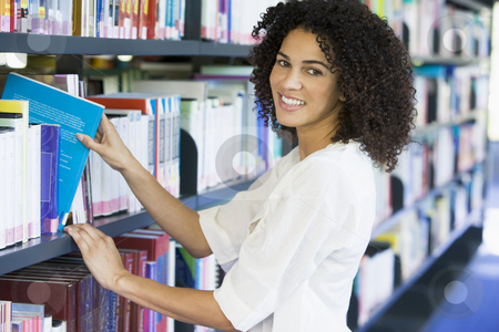 Woman pulling a library book off shelf stock photo,  by Monkey Business Images