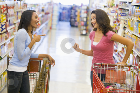 Two women meeting in supermarket stock photo, Two women meeting and chatting in supermarket aisle by Monkey Business Images