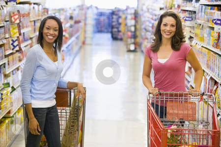 Two women meeting in supermarket stock photo, Two woman meeting in supermarket grocery ailse by Monkey Business Images