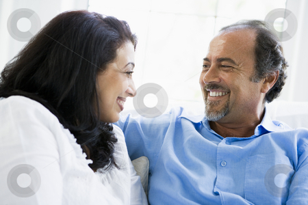 A Middle Eastern couple sitting at home stock photo,  by Monkey Business Images