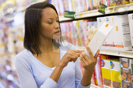 Female shopper checking food labelling stock photo, Female shopper checking food labelling in supermarket by Monkey Business Images