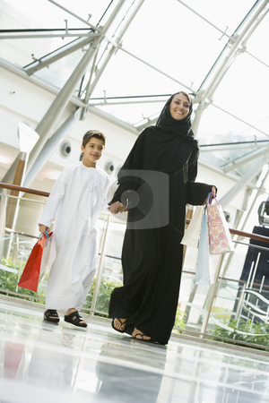 A Middle Eastern woman and her son in a shopping mall stock photo,  by Monkey Business Images