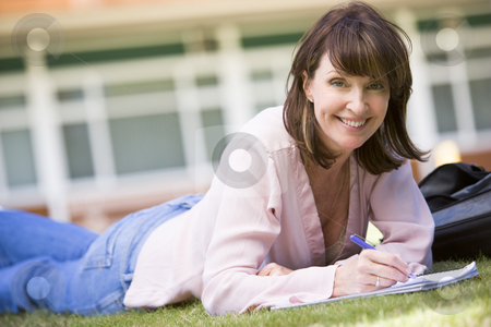 A woman writing notes while lying on a campus lawn stock photo,  by Monkey Business Images