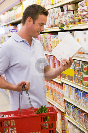 Man checking food labelling in supermarket stock photo, Man checking food labelling on supermarket products by Monkey Business Images