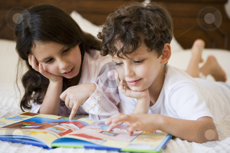A Middle Eastern brother and sister reading together stock photo,  by Monkey Business Images