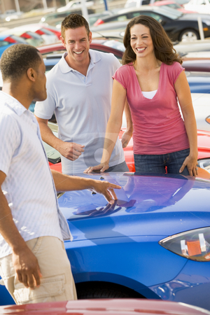 Couple discussing new car with salesman stock photo, Couple discussing new car with salesman on lot by Monkey Business Images