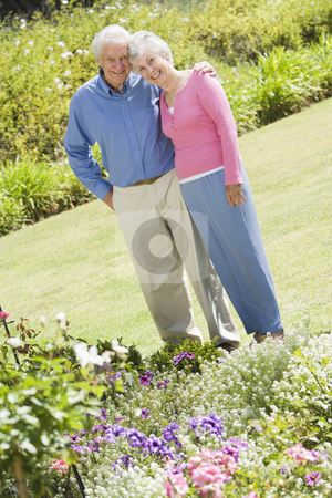 Senior couple standing in garden stock photo, Senior couple standing in garden admiring flowerbed by Monkey Business Images
