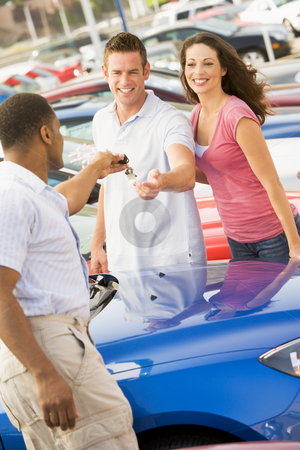 Young couple collecting new car stock photo, Young coupled collecting new car from salesman by Monkey Business Images