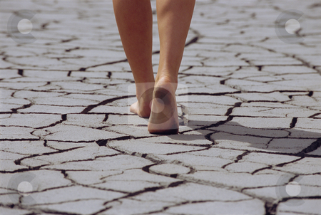 Woman walking barefoot across cracked earth, low section stock photo,  by Monkey Business Images