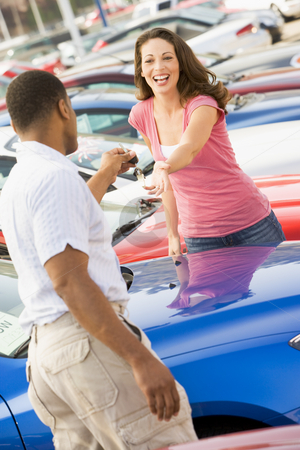 Woman picking up keys to new car stock photo, Woman picking up keys to new car from salesman by Monkey Business Images