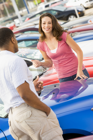 Woman talking to car salesman stock photo, Woman talking to car salesman at lot by Monkey Business Images