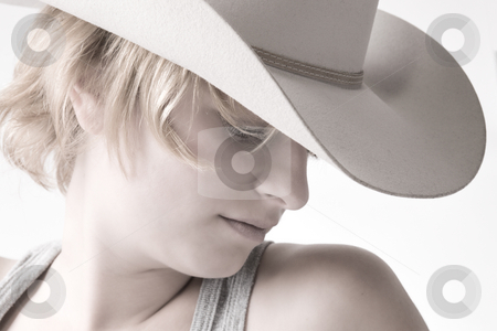 Portrait of a red haired Cowgirl stock photo, Studio portrait of a red haired girl with a cowboy hat looking down. by Frenk and Danielle Kaufmann