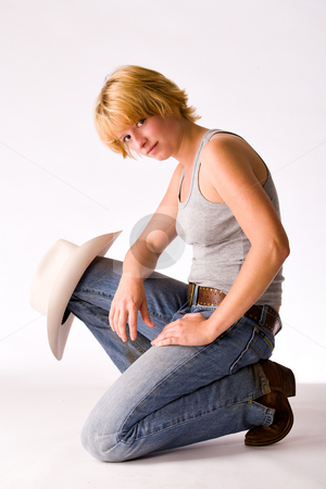 Portrait of a red haired Cowgirl sitting on her knee stock photo, Studio portrait of a cow-girl on one knee with her hat on her knee by Frenk and Danielle Kaufmann