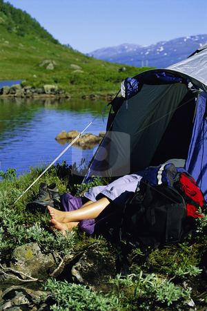 Young woman asleep in tent next to lake,  stock photo,  by Monkey Business Images