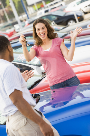Woman picking up keys to new car stock photo, Woman picking up keys to new car from lot by Monkey Business Images
