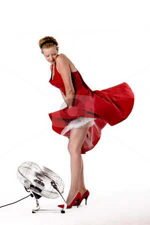 Funny girl in red gala dress playing with a ventilator stock photo, Girl in red gala dress making fun with te4h wind of a ventilator by Frenk and Danielle Kaufmann
