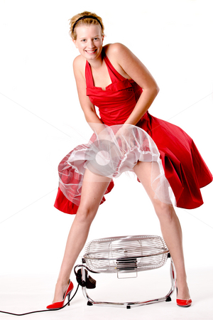 Funny girl in red gala dress that blows up with a ventilator stock photo, Girl in red gala dress making fun with a ventilator by Frenk and Danielle Kaufmann