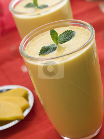 Glasses of Mango Lassi stock photo, Glasses of Mango Lassi with Mango Side by Monkey Business Images
