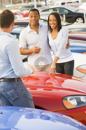 Young couple discussing new car with salesman stock photo, Young couple discussing new car with salesman on lot by Monkey Business Images